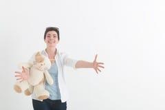 一件白色女衬衫的少妇有猫的准备拥抱某人,宽涂她的手分开并且招呼微笑 免版税图库摄影
