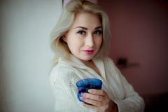 一件白色女衬衫的蓝眼睛的金发碧眼的女人在与一个蓝色杯子的一个窗口附近 库存照片
