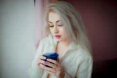 一件白色女衬衫的蓝眼睛的金发碧眼的女人在与一个蓝色杯子的窗口附近 库存照片
