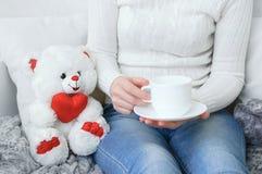 一件白色毛线衣和牛仔裤的女孩在有一杯咖啡的长沙发在他们的手上 免版税库存照片