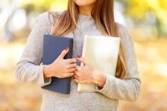 一件白色毛线衣的一个美丽的女孩拿着一本书和一种片剂在秋天公园背景  库存照片