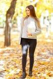 一件白色毛线衣的一个美丽的女孩拿着一本书和一种片剂在秋天公园背景  免版税库存照片