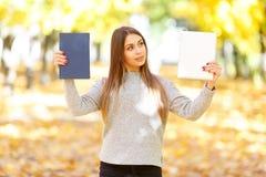 一件白色毛线衣的一个美丽的女孩拿着一本书和一种片剂在秋天公园背景  库存图片
