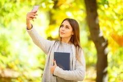一件白色毛线衣的一个美丽的女孩拿着一本书并且做在秋天公园背景的一selfie  库存图片