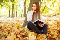 一件白色毛线衣的一个美丽的女孩拿着在秋天公园背景的一本书  库存照片