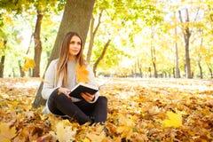 一件白色毛线衣的一个美丽的女孩拿着在秋天公园背景的一本书  免版税库存照片