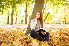 一件白色毛线衣的一个美丽的女孩拿着在秋天公园背景的一本书  免版税库存图片