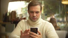 一件白色毛线衣的英俊的年轻人使用智能手机,坐在一个咖啡馆在城市在反对窗口 库存图片