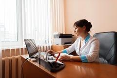 一件白色浴巾的一位女性医生在膝上型计算机后工作在一个窗口附近在医院 负责任的工作 库存图片