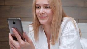 一件白色浴巾的一名年轻可爱的中年白肤金发的妇女在床上躺在酒店房间 写消息  股票录像