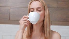 一件白色浴巾的一名年轻可爱的中年白肤金发的妇女在床上躺在酒店房间 调味的饮料 股票视频