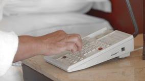 一件白色浴巾的未被认出的成人资深妇女在酒店房间告诉招待会,拨号码 t 股票录像