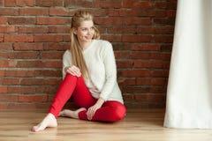 一件白色温暖的夹克的美丽的年轻白肤金发的妇女和红色zhdinsah,坐地板在窗口附近,对红砖墙壁 库存照片