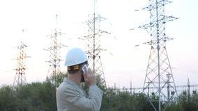 一件白色盔甲的驻地技术主任在发电站和谈话站立在有工作者的电话附近 股票录像