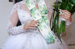 一件白色礼服有花束的和金钱诗歌选的新娘从50以色列锡克尔的 库存照片