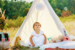 一件白色礼服的一个女孩在一个白色帐篷坐绿色灌木背景  坐他的腰臀部分的孩子 免版税库存照片