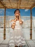 一件白色礼服的一个女孩在大阳台 面孔在树荫下 镶边的影子 休息,假期,旅行 突尼斯 图库摄影