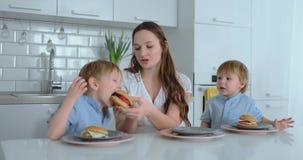 一件白色礼服的一个年轻美丽的母亲有两个孩子的是微笑和吃新鲜的汉堡在她的厨房里 ?? 股票视频