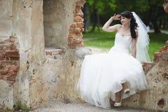 一件白色礼服的一个美丽的新娘坐废墟并且调查距离 免版税库存图片