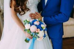 一件白色礼服的一套蓝色无尾礼服的新娘和新郎在窗口旁边站立并且拿着婚礼花束 免版税库存图片