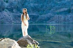 一件白色礼服的一美女有dreadlocks的在湖站立 日出的湖 免版税库存图片