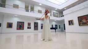 一件白色礼服的夫人在弹在画廊的小提琴 股票视频