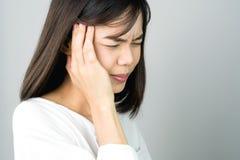 一件白色礼服的妇女是显示她的头疼的感人的头 原因也许由重音或偏头痛造成 免版税图库摄影