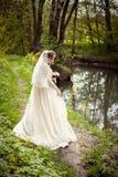 一件白色礼服的新娘在自然背景  婚姻的摄影 免版税库存照片
