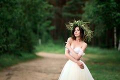 一件白色礼服的新娘有花花圈的  免版税库存照片