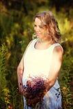 一件白色礼服的美丽和愉快的孕妇在自然在夏天,在树和花附近 免版税库存照片