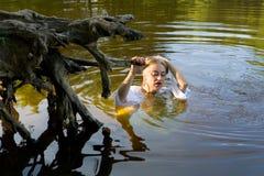 一件白色礼服的美丽的女孩在水中 库存图片