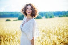 一件白色礼服的美丽的妇女在麦田 免版税库存图片