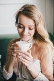 一件白色礼服的美丽的年轻白肤金发的妇女享用与泡沫的咖啡热奶咖啡 免版税库存照片