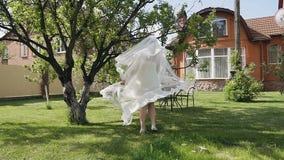 一件白色礼服的美丽的新娘有围绕并且早晨走在的一个晴天的一根长的鞋带的 股票录像