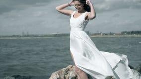 一件白色礼服的美女在海滨站立 妇女拿着在风慢动作振翼的一件礼服 影视素材
