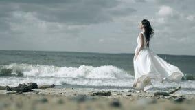 一件白色礼服的美女在海滨站立 妇女拿着在风慢动作振翼的一件礼服 股票视频