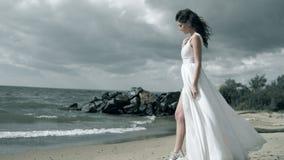一件白色礼服的美女在海滨站立 振翼在风慢动作的礼服 影视素材