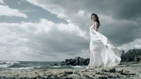 一件白色礼服的美女在海滨站立 振翼在风慢动作的礼服 股票视频