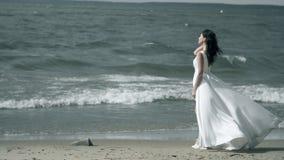 一件白色礼服的美女在海滨站立 振翼在风慢动作的礼服 股票录像