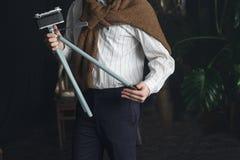 一件白色衬衣和一件棕色毛线衣的一个人拿着有照相机的,葡萄酒一个老三脚架 图库摄影