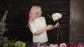一件白色衬衣的愉快,美丽的女孩卖花人从一个宽分类热心地选择构成的花 影视素材