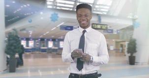 一件白色衬衣的非裔美国人的黑人读消息的在一个手机 影视素材