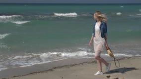 一件白色透明礼服的年轻美女有飞行在沿海滨的风步行的白发的和 股票录像