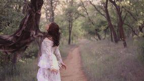 一件白色透明长的礼服的逗人喜爱的女孩有一头花卉样式和黑暗的波浪发的由精神抓住  股票视频