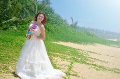 一件白色通风礼服的一个年轻新娘站立与莲花花束  微笑在海岛上的一个热带海滩的女孩 免版税库存照片