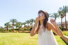 一件白色长的礼服的一个女孩在一棵热带棕榈走送空气亲吻到照相机 库存图片