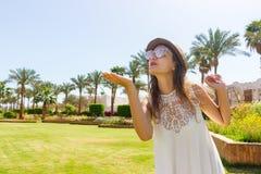 一件白色长的礼服的一个女孩在一棵热带棕榈走送空气亲吻到照相机 免版税库存图片