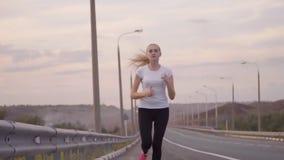 一件白色T恤杉和光运动鞋的一个运动的女孩沿在城市之外的一条空的轨道跑 美丽的森林 股票录像