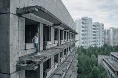 一件白色T恤杉和蓝色牛仔裤的一个女孩及早站立在一个被破坏的大厦的一个被破坏的阳台边缘  免版税库存图片
