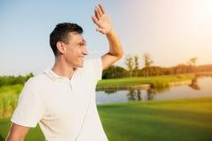 一件白色T恤杉的一个人在高尔夫球场站立并且微笑着在明亮的太阳覆盖下 库存照片